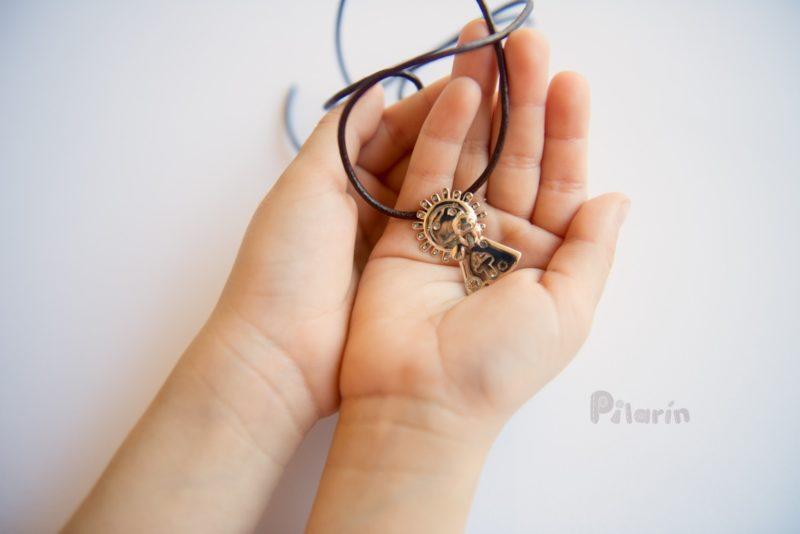 Medalla Pilarín de plata en manos niña